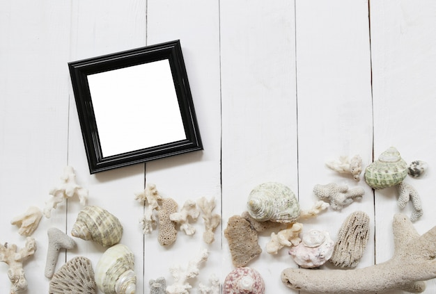 Zwarte houten fotolijst op een witte houten vloer en hebben schelpen en koraalriffen.