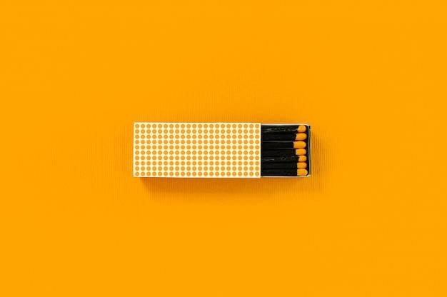 Zwarte houten overeenkomsten met gele hoofden in creatief gestippeld document vakje op gewaagde gele achtergrond.