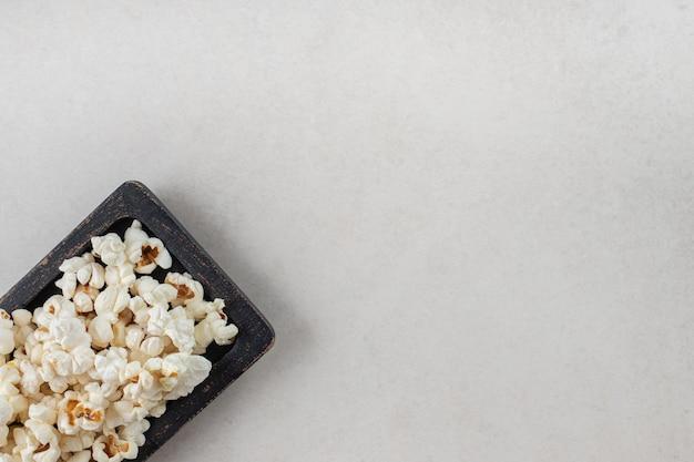 Zwarte houten schotel met knapperige popcorn op marmeren tafel.