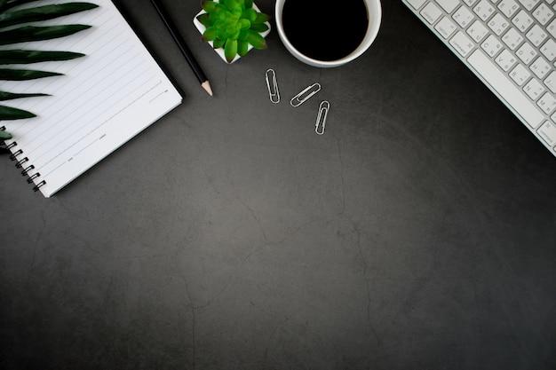 Zwarte houten tafel met smartphone, laptop, koffie, bladeren en accessoires werk.