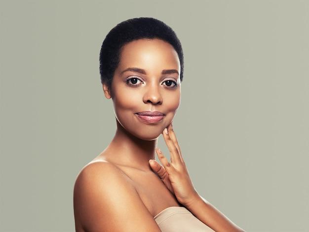 Zwarte huid schoonheid vrouw gezond haar huid sluiten afro-amerikaanse mooi model met handen. op grijs.