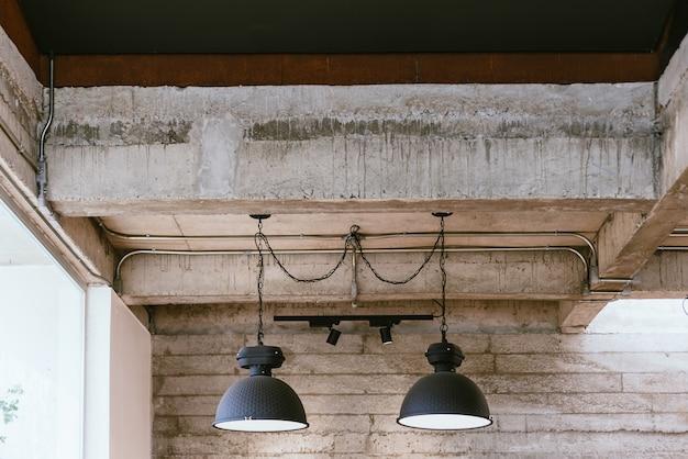 Zwarte ijzeren elektrische lampen opgehangen aan stalen kettingen van de betonnen balk loft en industrieel interieur
