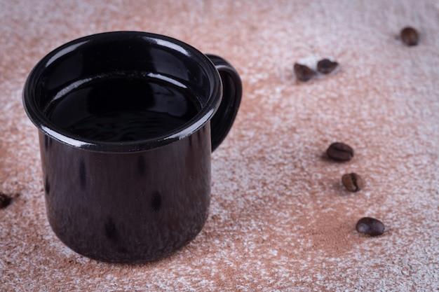 Zwarte ijzeren mok met koffie op tafel