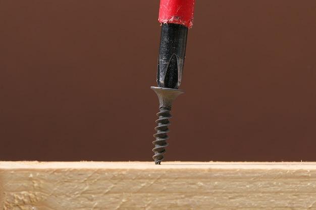 Zwarte ijzeren schroeven die met een schroevendraaier in hout worden geschroefd. bevestigingsmiddelen en hardware.