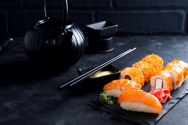 Zwarte ijzeren theepot en sushi op leisteen plaat op zwarte stenen tafel