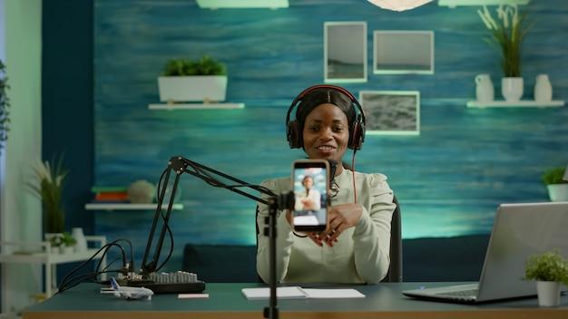 Zwarte influencer in de entertainmentindustrie die praat en geluid controleert tijdens uitzending vanuit thuisstudio. on-air online productie internet podcast show host streaming live content voor sociale media