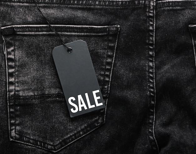 Zwarte jeans met een close-up van het verkooplabel. seizoensgebonden kortingen