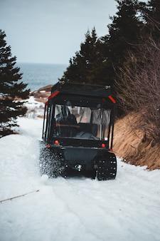 Zwarte jeepworstelaar op sneeuw behandelde grond overdag