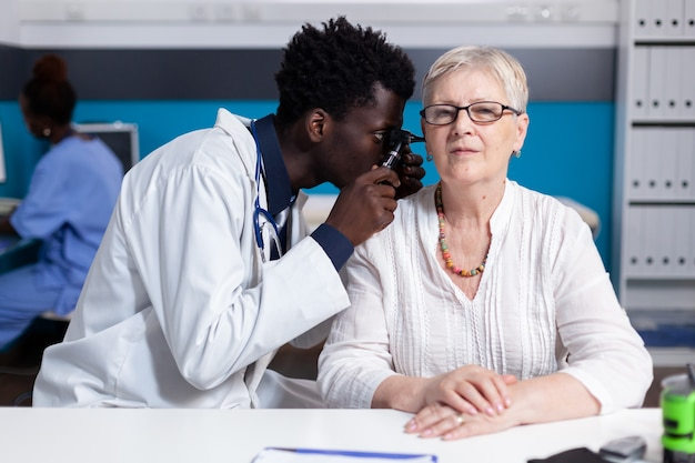 Zwarte jonge dokter die otoscoop gebruikt op oudere patiënt