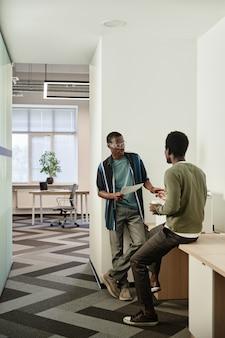 Zwarte jonge kantoormedewerkers maken kopieën van rapporten en contracten en bespreken een groot project dat ze...