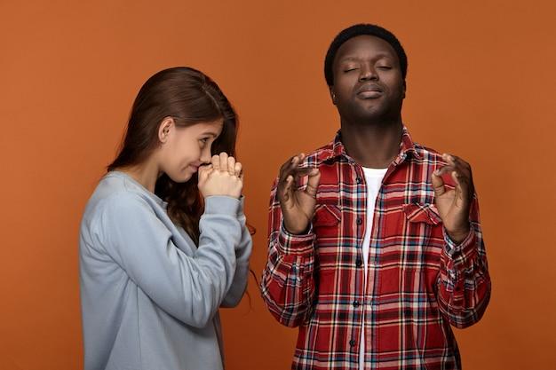 Zwarte jonge kerel die mudra-gebaar maakt en de ogen gesloten houdt, probeert te kalmeren terwijl hij een geschil of onenigheid heeft met zijn koppige blanke vrouw. portret van sex tussen verschillendre rassen paar bidden