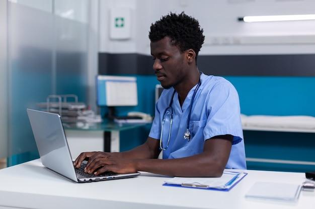 Zwarte jonge man aan het werk als verpleegster bij medische kliniek