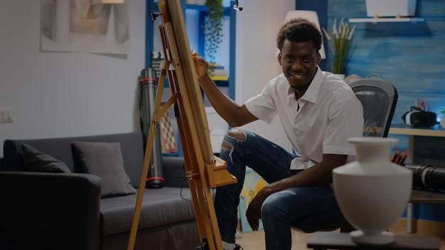 Zwarte jonge volwassene die in de tekeningsvaas van de kunstwerkstudio zit