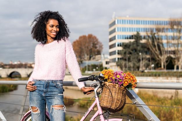 Zwarte jonge vrouw die een uitstekende fiets berijdt
