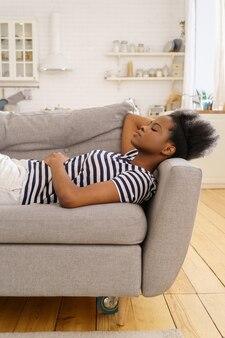 Zwarte jonge vrouw draagt gestripte t-shirt rusten slapen op de bank thuis gesloten ogen een pauze nemen
