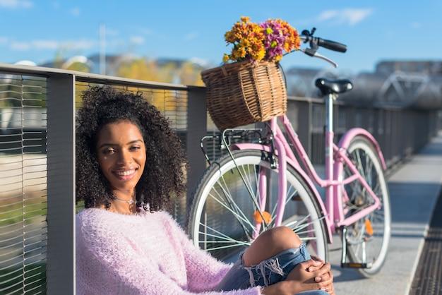 Zwarte jonge vrouwenzitting door de rivier met haar uitstekende fiets