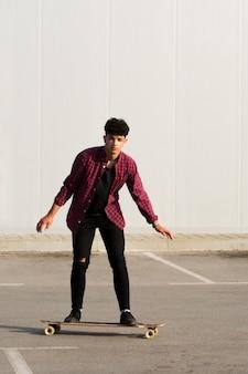 Zwarte jongeman in zwart denim rijden skateboard