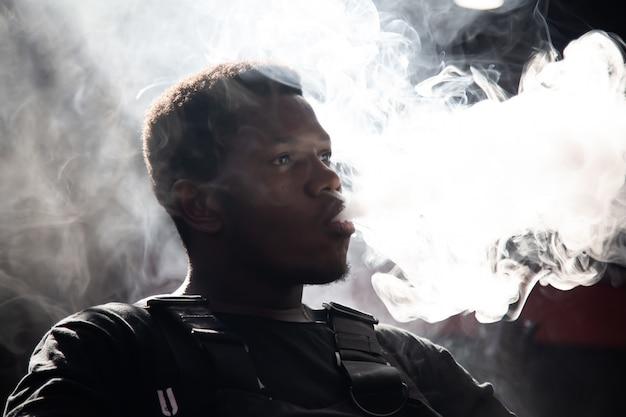 Zwarte jongen blaast rook uit zijn mond terwijl in een donkere kamer zit