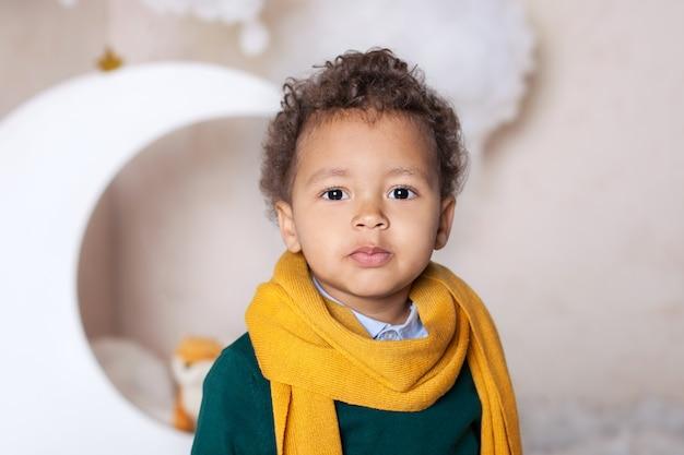 Zwarte jongen close-up. portret van een vrolijk lachende zwarte jongen in een gele sjaal. portret van een kleine afro-amerikaanse. zwarte man. nadenkend kind. kindertijd. kind speelt in de kleuterschool. kleine jongen gezicht