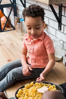 Zwarte jongen dichtbij pan met deegwaren die duim tonen