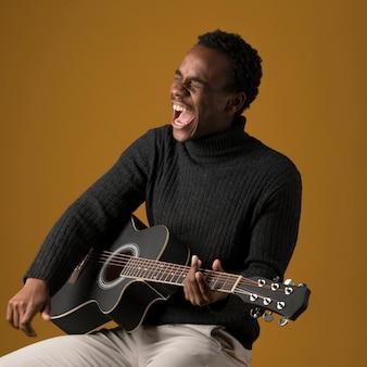Zwarte jongen die de gitaar speelt