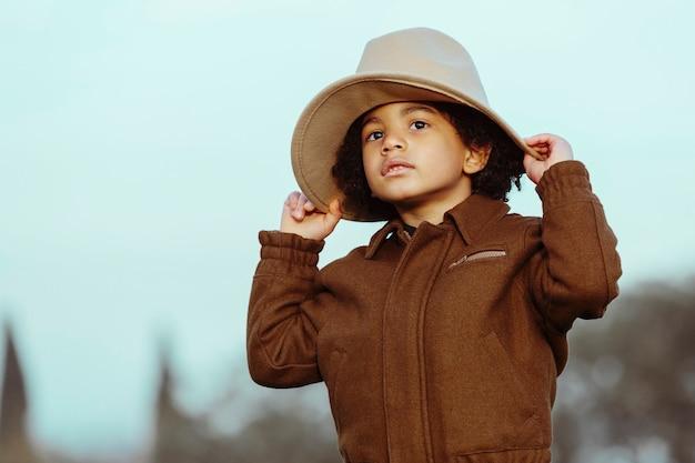 Zwarte jongen die een cowboyhoed draagt. op een parkachtergrond. . afbeelding met copyspace. kinderen en zwarte mensen concept