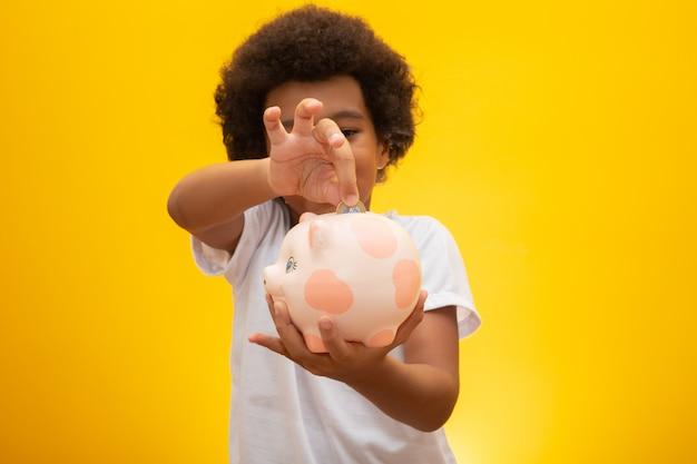 Zwarte jongen die geld verzamelt aan spaarvarken. kleine jongen geld steken in spaarvarken voor toekomstige besparingen, multicultureel samen onderwijs