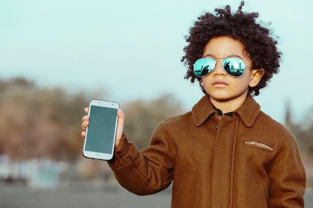 Zwarte jongen met afrohaar en zonnebril, die zijn mobiele telefoon toont. op een parkachtergrond. kinderen, smartphones en zwarte mensen concept. afbeelding met copyspace