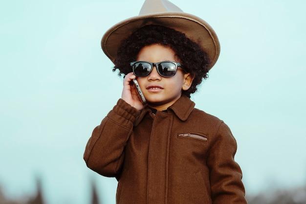 Zwarte jongen met cowboyhoed en zonnebril, praten over zijn mobiele telefoon. op een parkachtergrond. kinderen, smartphones en zwarte mensen concept
