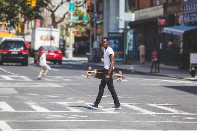 Zwarte jongen wandelen in de stad met longboard