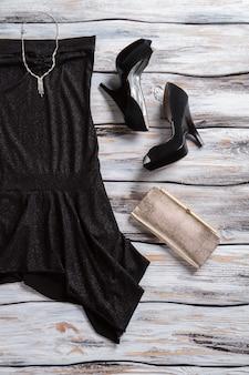 Zwarte jurk en zilveren portemonnee donkere hak schoenen en sieraden luxe kleding voor jonge dames charme en ...