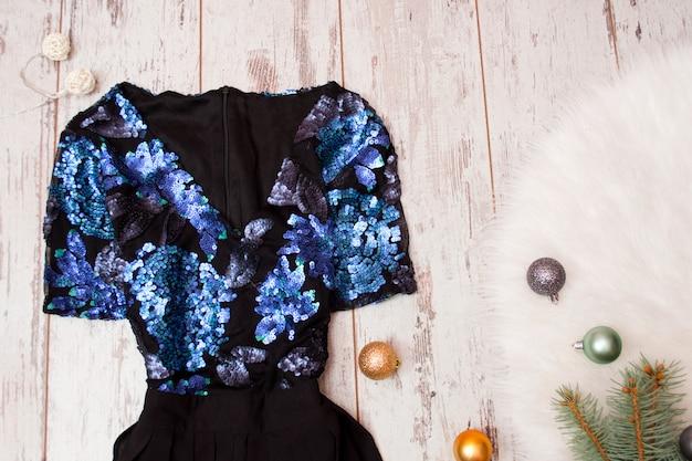 Zwarte jurk met blauwe pailletten, kerstballen op wit bont. modieus concept, bovenaanzicht
