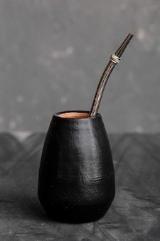 Zwarte kalebas met nippend metalen stro