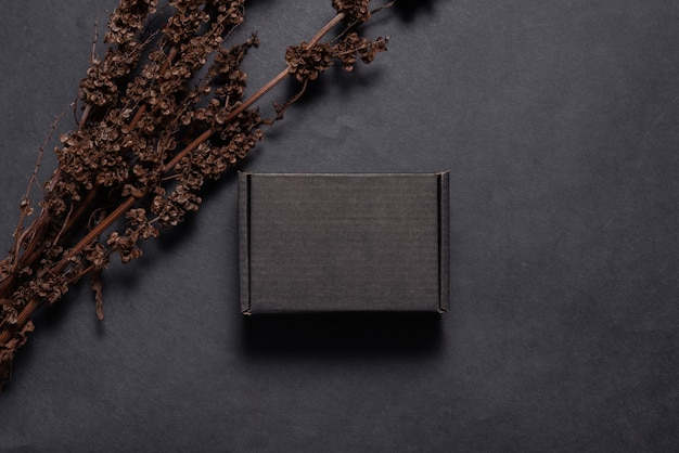 Zwarte kartonnen kartonnen doos versierd met gedroogde tak mock up