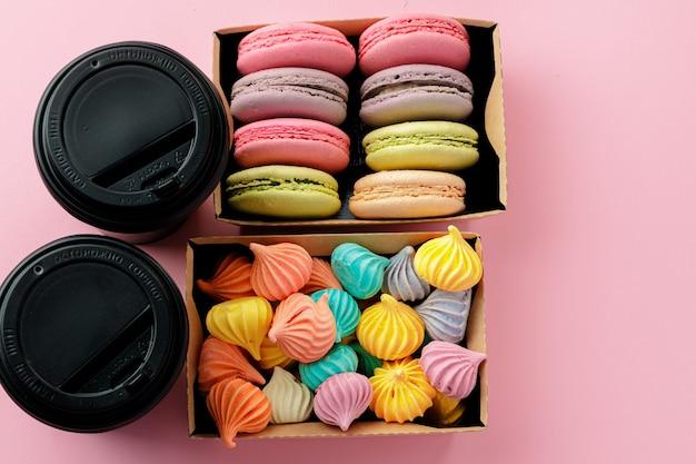 Zwarte kartonnen koffiekopje met doos met kleurrijke meringue cookies op roze