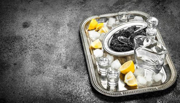 Zwarte kaviaar en wodka op rustieke tafel.
