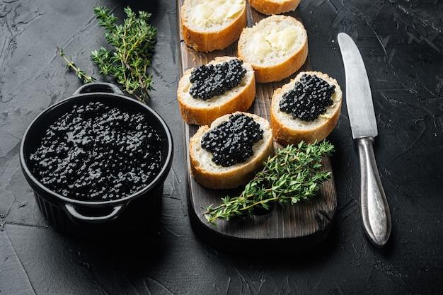 Zwarte kaviaar geserveerd op stokbrood, op zwarte tafel