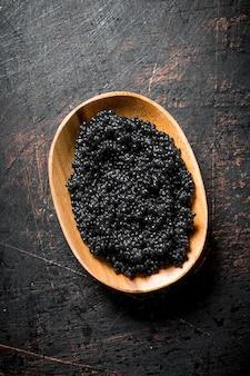 Zwarte kaviaar in de kom. op donkere rustieke tafel