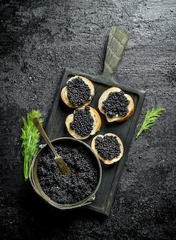 Zwarte kaviaar in een kom en sandwiches met kaviaar op een snijplank met dille. op zwarte rustieke ondergrond