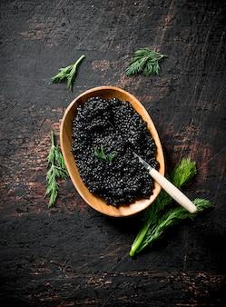 Zwarte kaviaar in een kom met dille. op rustieke ondergrond