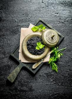 Zwarte kaviaar in een kom op een snijplank met peterselie. op zwarte rustieke ondergrond