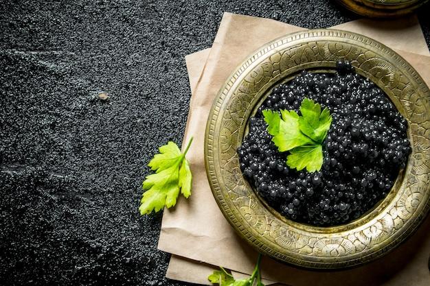 Zwarte kaviaar in een kom op papier met peterselie. op zwarte rustieke tafel