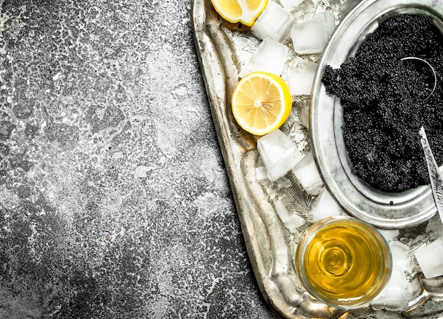 Zwarte kaviaar met witte wijn en schijfjes citroen op rustieke tafel.
