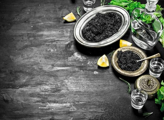 Zwarte kaviaar met wodka en schijfjes citroen. op een zwart bord.