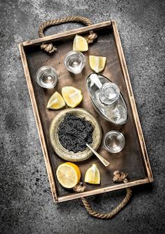 Zwarte kaviaar met wodka op een oud dienblad. op rustieke achtergrond.