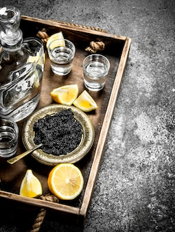 Zwarte kaviaar met wodka op oud dienblad op rustieke lijst.