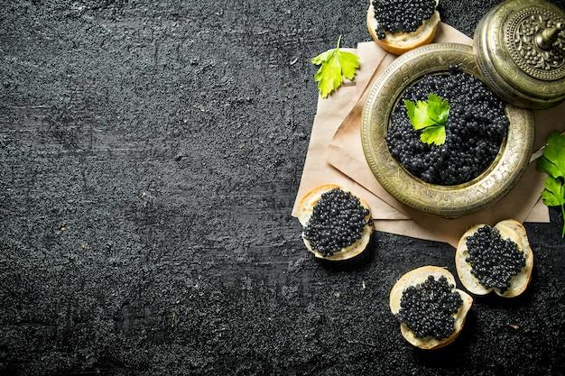 Zwarte kaviaar op sneetjes brood en kaviaar in een kom op papier met peterselie. op zwarte rustieke ondergrond