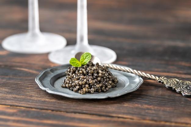 Zwarte kaviaar op zilveren vintage plaatclose-up