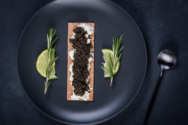 Zwarte kaviaar van steur in de koekjes met roomkaas. lepel met kaviaar. rond blauw bord. donker oppervlak