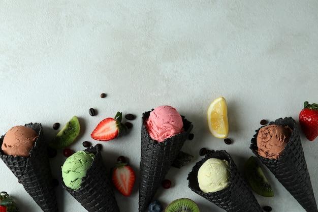 Zwarte kegels met roomijs en ingrediënten op geweven wit